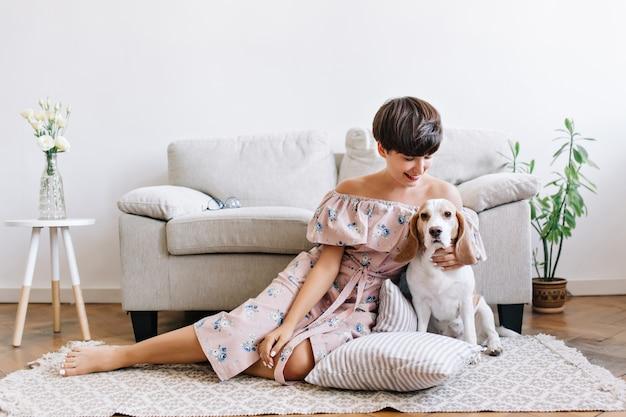 Blij jonge vrouw met glanzend bruin haar poseren op de vloer met haar schattige beagle puppy. indoor portret van opgewonden meisje in jurk met bloemenprint zittend op het tapijt met hond Gratis Foto