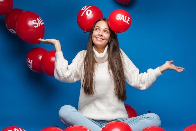 Blij jonge vrouw zitten en kijken op verkoop rode lucht ballonnen, geïsoleerd op blauwe muur Premium Foto
