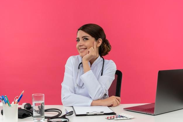 Blij jonge vrouwelijke arts het dragen van medische mantel met stethoscoop zit aan bureau werken op computer met medische hulpmiddelen hand op wang zetten met kopie ruimte Gratis Foto