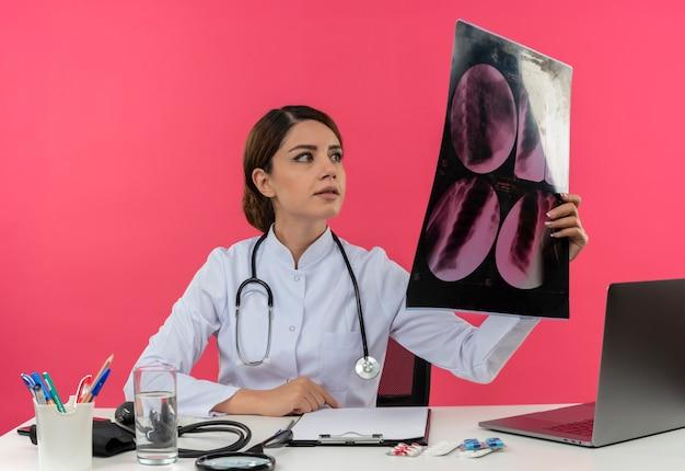 Blij jonge vrouwelijke arts medische gewaad dragen met een stethoscoop zit aan bureau werken op computer met medische hulpmiddelen houden en kijken naar x-ray met kopie ruimte Gratis Foto