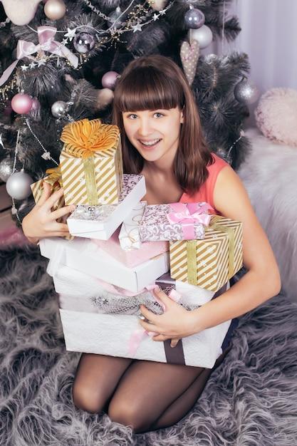 Blij kaukasisch meisje knuffelt een berg kerstcadeautjes in witte verpakking Premium Foto