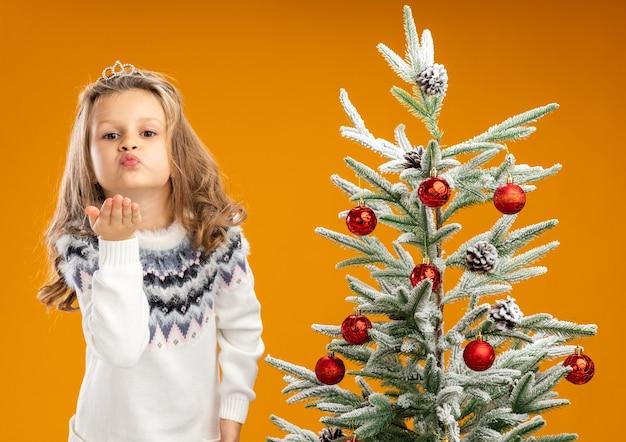Blij meisje dat zich dichtbij kerstboom bevindt die tiara met slinger op hals draagt die kusgebaar toont dat op oranje achtergrond wordt geïsoleerd Gratis Foto