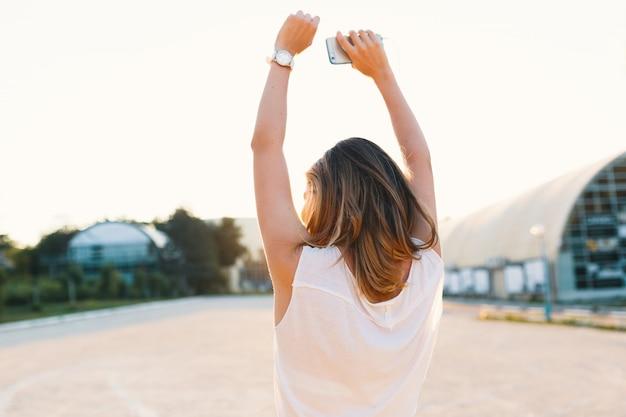 Blij meisje die in de straat op een zonnige dagholdings omhoog dansen Gratis Foto