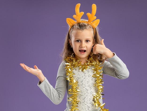Blij meisje met kerst haar hoepel met slinger op nek met telefoongesprek gebaar en punten aan de zijkant geïsoleerd op blauwe achtergrond met kopie ruimte Gratis Foto