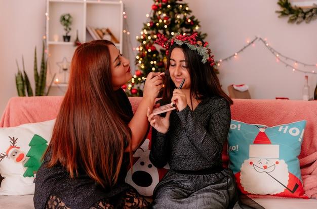 Blij moeder doet make-up voor haar dochter met hulst krans zittend op de bank genieten van kersttijd thuis Gratis Foto