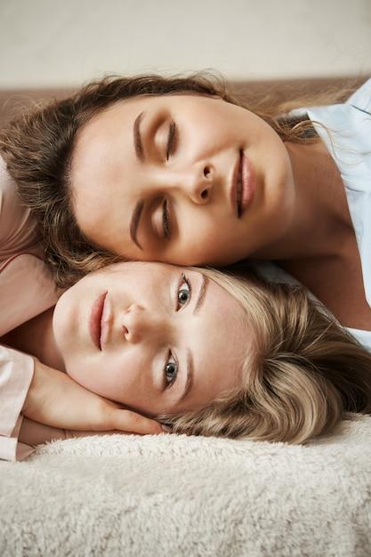 Blij om soulmate te vinden om haar gedachten te delen. verticaal schot van aantrekkelijk blondemeisje die op bank met haar vriendin liggen die op haar hoofd liggen, breed glimlachend, thuis ontspannen en gezellig voelen Gratis Foto