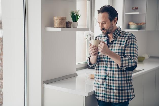 Blij optimistisch rusten knap aardig blij in goed humeur man kopje heerlijke koffie bedrijf in handen staan in de buurt van groot raam Premium Foto
