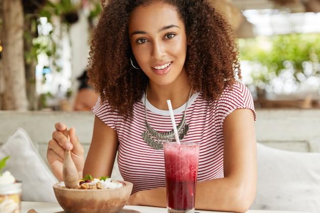 Blij positieve jonge studente geniet van zomervakanties in het buitenland, brengt vrije tijd door in café, eet salade en rode smoothie, nonchalant gekleed, is graag in goed gezelschap. mensen en levensstijlconcept Gratis Foto