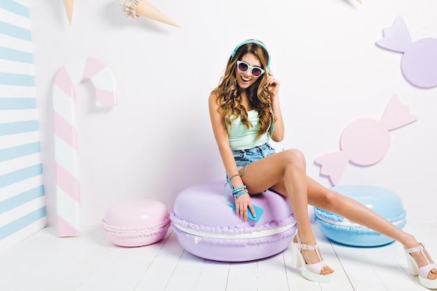 Blij slank meisje met lange benen zittend op grote paarse makaron en lachen. indoor portret van mooie jonge vrouw in witte schoenen rusten in haar kamer en luisteren muziek in koptelefoon. Gratis Foto