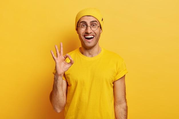 Blij tevreden man toont ok gebaar of goedkeuringsteken, geeft positief antwoord, beweert dat alles in orde is Gratis Foto