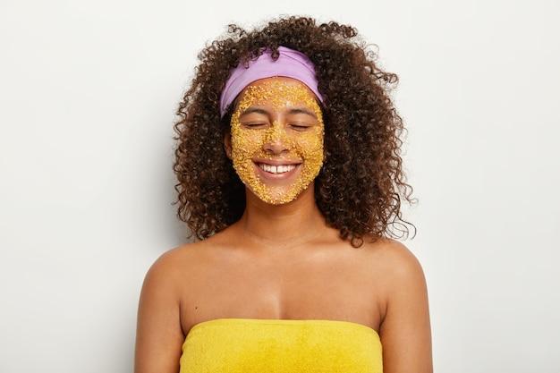 Blij tevreden vrouw met afro-kapsel maakt natuurlijke gezichtsscrub met gele zeezout, krijgt een gladdere huid, verwijdert irritatie en donkere vlekken, verbetert de mineralenbalans, heeft schoonheidsroutine, gewikkeld in een handdoek Gratis Foto