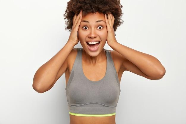 Blij verrast vrouw houdt beide handen op het hoofd, reageert op geweldige relevantie, heeft mond open, gekleed in grijze beha Gratis Foto