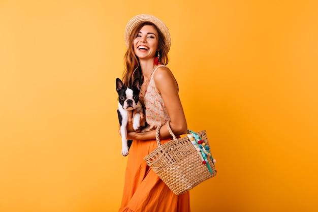 Blij vrouw die in zomerhoed franse bulldog houdt. lachend meisje in oranje rok poseren met grappige puppy. Gratis Foto