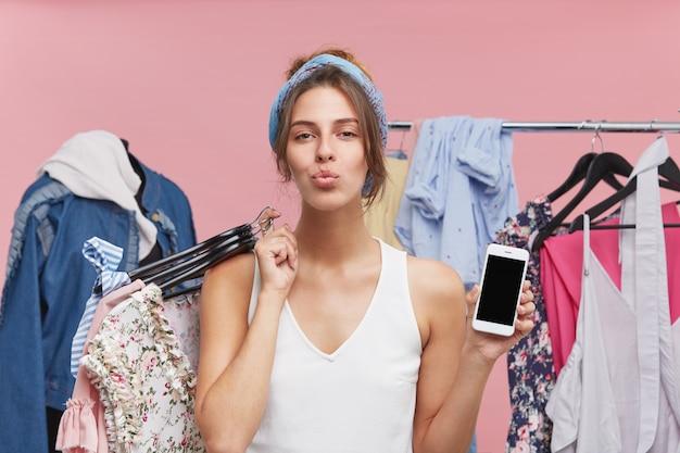 Blij vrouwelijk model dat op haar lippen drukt, tegen manequin en rek met kleren staat, hagers met kledingstuk en mobiele telefoon met een leeg scherm vasthoudt, een goed humeur heeft na succesvol winkelen Gratis Foto