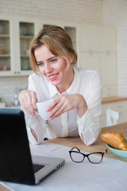 Blije bedrijfsvrouw met koffie die laptop met behulp van Gratis Foto