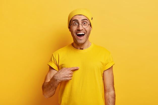 Blije blanke man wijst vrolijk naar zichzelf, heeft een vreugdevolle blik verrast, vraagt of hij precies de wedstrijd heeft gewonnen Gratis Foto