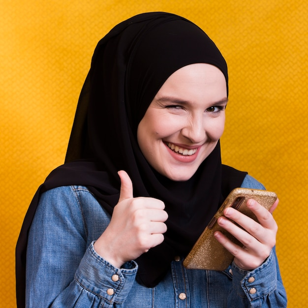 Blije cellphone van de vrouwenholding die thumbup tegen gele oppervlakte gesturing Gratis Foto