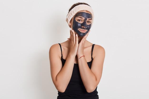 Blije europese vrouw brengt voedend kleimasker aan op gezicht, heeft blije uitdrukking, raakt wangen aan, heeft een probleem met een droge huid. Gratis Foto