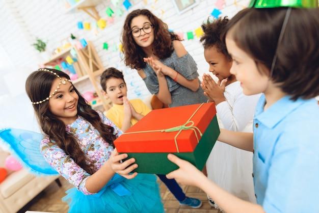Blije feestvarken in feestelijke hoed ontvangt geschenk. Premium Foto