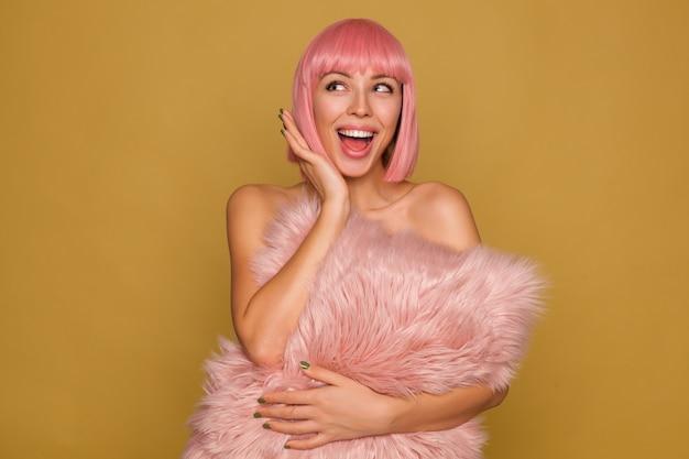Blije jonge aantrekkelijke roze harige vrouw met groene manicure die vrolijk opzij kijkt en haar mond wijd open houdt, pluizig kussen over mosterdmuur houdt Gratis Foto