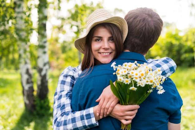 Blije jonge vrouw die vriend in park omhelst Gratis Foto