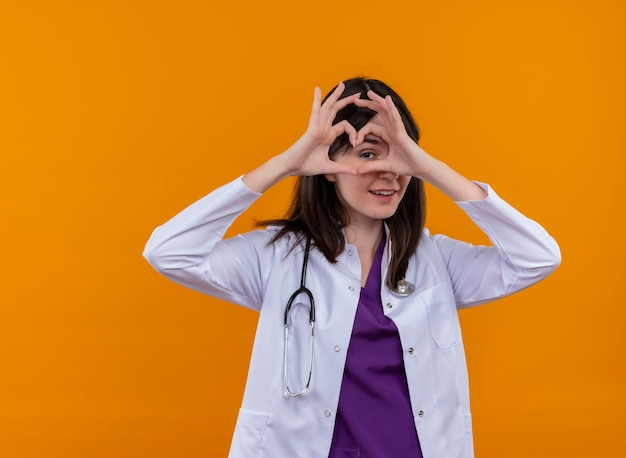 Blije jonge vrouwelijke arts in medisch kleed met het hart van stethoscoopgebaren met beide handen op geïsoleerde oranje achtergrond met exemplaarruimte Gratis Foto