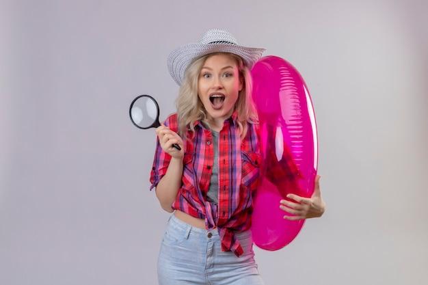 Blije jonge vrouwelijke reiziger die rood overhemd in hoed draagt die opblaasbare ring en meer magnifier op geïsoleerde witte muur houdt Gratis Foto