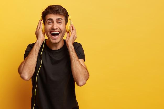 Blije mannelijke meloman geniet van het aangename geluid van een nieuwe koptelefoon, luistert naar favoriete muziek Gratis Foto