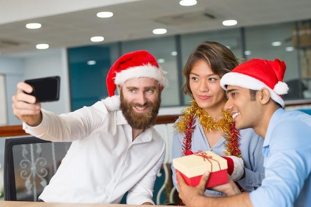 Blije multi-etnische werkgroep die van de partij van kerstmis van kerstmis geniet Gratis Foto