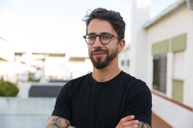 Blije stijlvolle man in glazen die zich voordeed op appartement balkon Gratis Foto