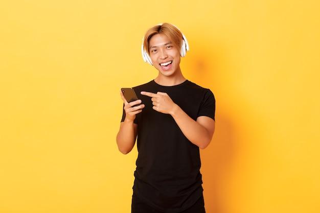 Blije tevreden aziatische knappe kerel, luistert muziek of goede podcast in hoofdtelefoons, wijzende vinger naar smartphone met tevreden glimlach, gele muur Gratis Foto