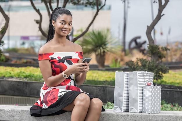Blije volwassen afrikaanse amerikaanse vrouw die met smartphone interactie aangaan terwijl het zitten op bank tegen winkelcentrum Premium Foto