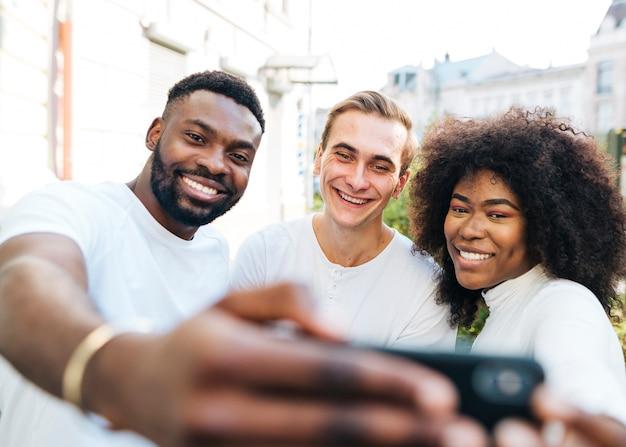 Blije vrienden buiten nemen selfie Gratis Foto