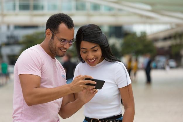 Blije vrienden die zich op straat bevinden en smartphone gebruiken Gratis Foto