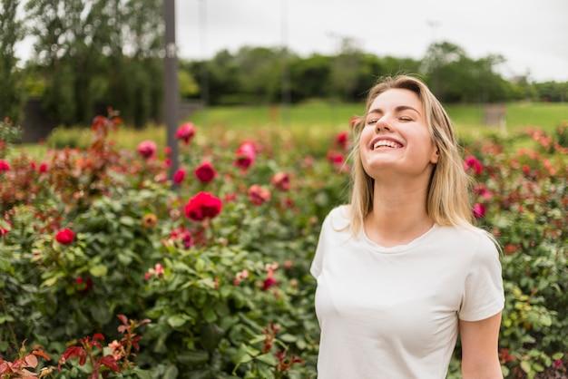 Blije vrouw die zich in bloemtuin bevindt Gratis Foto