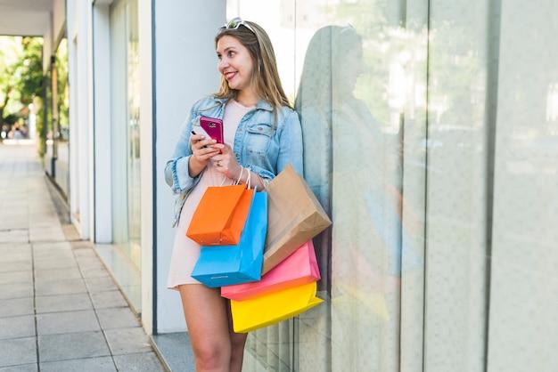 Blije vrouw die zich met het winkelen zakken, smartphone en creditcard bevindt Gratis Foto