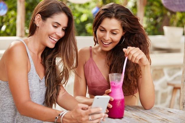 Blije vrouwelijke modellen kiezen een foto om bij te werken in sociale netwerken, bekijk afbeeldingen op een smartphone met blije uitdrukkingen Gratis Foto