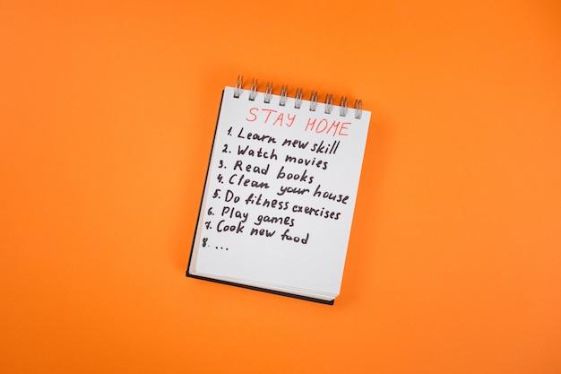 Blijf thuis checklist geschreven op het notitieblok op de oranje achtergrond. blijf thuis in quarantaine tijdens covid 19 pandemie. Premium Foto