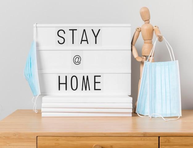 Blijf thuis inscriptie met houten mannequin en medische maskers Premium Foto