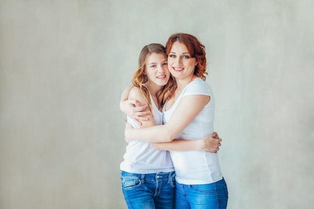 Blijf thuis mam, blijf veilig. jonge moeder die haar kind omhelst. vrouw en tiener het ontspannen in witte slaapkamer dichtbij grijze muur binnen. gelukkige familie thuis. jonge moeder spelen whith haar dochter. Premium Foto