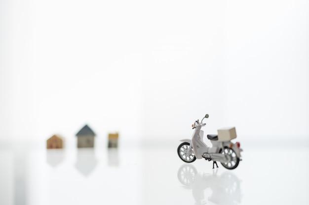 Blijf thuis, shelter in place met levering en winkelen online concept. sluit omhoog van scotter / motorfiets met containerdoos en minihuis als achtergrond. Premium Foto