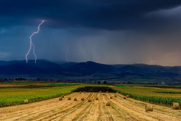 Bliksem over het veld. onweersbui en bliksem over het landbouwgebied. Premium Foto