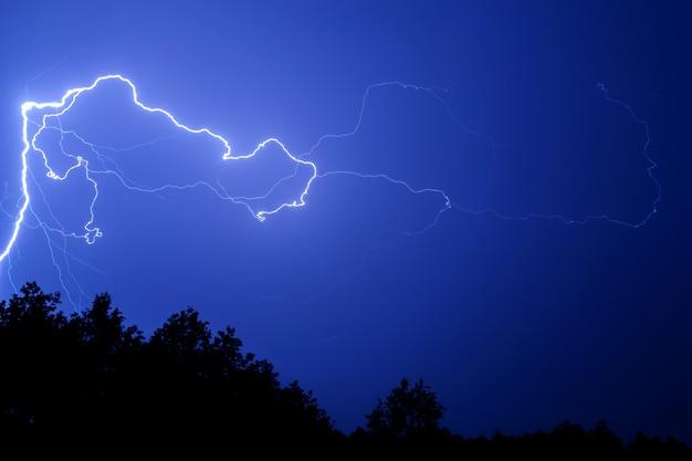Bliksem tegen een blauwe nachthemel boven de bomen. Premium Foto