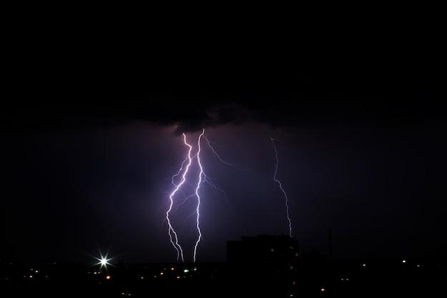 Bliksemweer over de stad in paars licht. Premium Foto