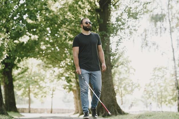 Blinde man. mensen met een handicap, gehandicapte persoon en het dagelijks leven. slechtziende man met wandelstok, trappen aflopend in stadspark. Gratis Foto