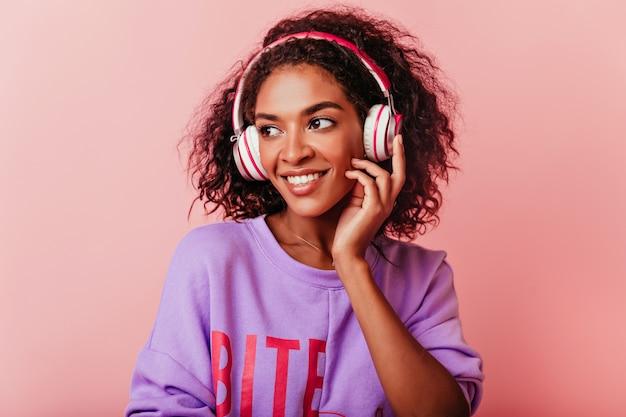 Blithesome zwart meisje luisteren muziek op pastel. winsome afrikaanse vrouw in paarse trui poseren in koptelefoon. Gratis Foto