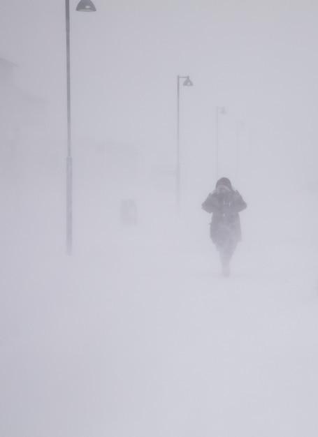 Blizzard in longyearbyen, vrouw die in sneeuwval loopt. abstracte wazig winterweer achtergrond Premium Foto