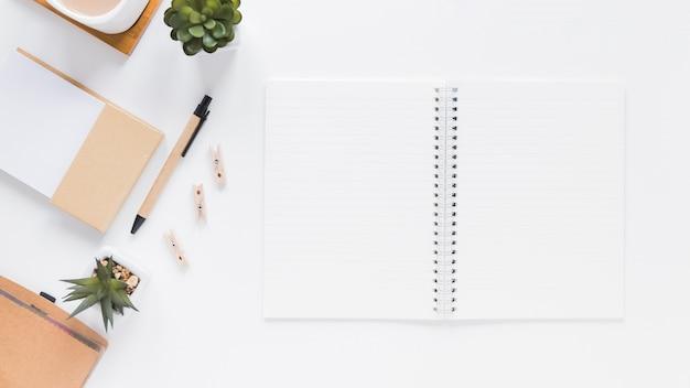 Blocnote dichtbij kantoorbehoeften en bloempotten op witte lijst Gratis Foto