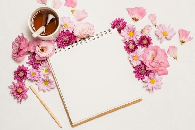 Blocnote dichtbij reeks van bloemen en kop van drank Gratis Foto