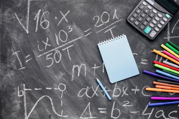 Blocnote en calculator met gevoelde pennen die op geschreven bord worden geschikt Gratis Foto